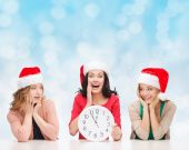 Smiling women in santa helper hat with clock — Photo