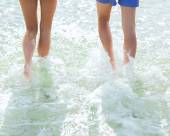 Close up of human legs on summer beach — Stock Photo