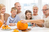 Happy family sitting with pumpkins at home — Foto de Stock