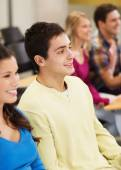 Group of smiling students in lecture hall — Stock Photo