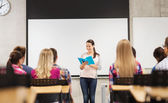 Group of smiling students in classroom — Stockfoto
