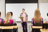 Group of smiling students in classroom — Stock Photo