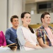 Group of smiling students in lecture hall — Stock Photo #54440593