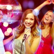 Three smiling women dancing and singing karaoke — Stock Photo #54503825