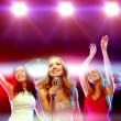 Three smiling women dancing and singing karaoke — Stock Photo #54503849