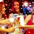 Three smiling women with cocktails in club — Stock Photo #54504373