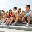 Group of smiling friends sitting on city square — Stock Photo #54507051