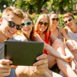 Smiling friends with tablet pc making selfie — Stock Photo #54507195