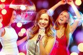 Three smiling women dancing and singing karaoke — Foto Stock