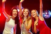 Tre donne sorridenti, ballando e cantando karaoke — Foto Stock
