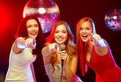 Three smiling women dancing and singing karaoke — Zdjęcie stockowe