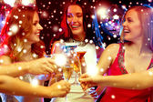 Three smiling women with cocktails in club — Foto Stock