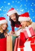 Smiling young women in santa hats with gifts — Foto Stock