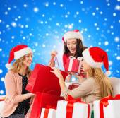 Smiling young women in santa hats with gifts — Stock Photo