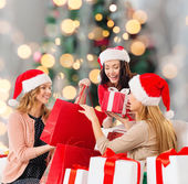Smiling young women in santa hats with gifts — Photo