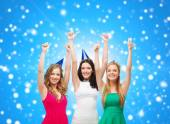 Smiling women in party caps showing thumbs up — Stockfoto