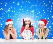 Lachende vrouw in santa helper hoeden met klok — Stockfoto