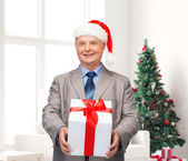 Glimlachende man in pak en santa helper hoed met cadeau — Stockfoto
