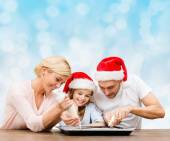 Happy family in santa helper hats cooking — Stock Photo
