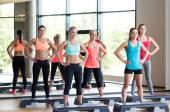 Groupe de femmes qui travaillent avec les steppers dans la salle de gym — Photo