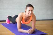 Smiling woman doing exercises on mat in gym — Foto de Stock
