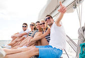 Smiling friends sitting on yacht deck — Stockfoto