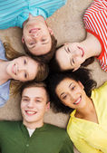Group of smiling people lying down on floor — Stock Photo