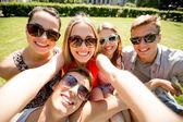группа улыбающихся друзей, делая селф в парке — Стоковое фото