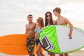 Smiling friends in sunglasses with surfs on beach — Foto de Stock