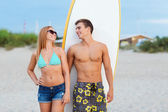 Smiling couple in sunglasses with surfs on beach — Stock Photo