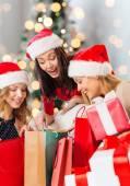Sourire des jeunes femmes à chapeaux santa avec cadeaux — Photo