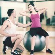 Male trainer with woman doing crunches on the ball — Stock Photo #54629939