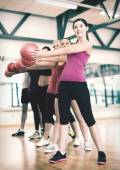 Group of smiling people working out with ball — Stockfoto