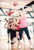 Group of smiling people working out with ball — Photo