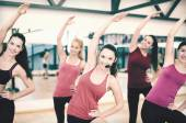 Group of smiling people stretching in the gym — Foto de Stock