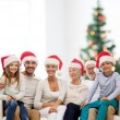 Happy family in santa helper hats sitting on couch — Stock Photo #54636049