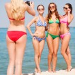 Group of smiling women photographing on beach — Stock Photo #54637451