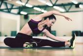 Stretching young woman with earphones in the gym — Stok fotoğraf
