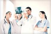 Young group of doctors looking at x-ray — Stock Photo