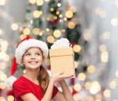 Lachende meisje in helper kerstmuts met een doos van de gift — Stockfoto