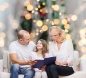 Glückliche familie mit buch zu hause — Stockfoto