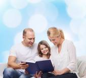 Happy family with book at home — Stockfoto