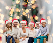 Happy family in santa helper hats sitting on couch — Stock Photo