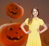 Smiling girl in dress over pumpkins background — Stock Photo