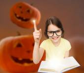 Smiling girl in glasses over pumpkins background — Stock Photo