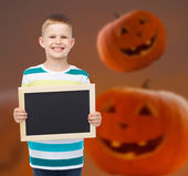 Smiling little boy with black board — Stock Photo