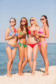 Group of smiling women eating ice cream on beach — Stok fotoğraf