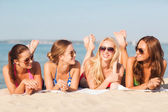 Group of smiling women in sunglasses on beach — Stock Photo