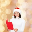 Smiling woman in santa hat with greeting card — Stock Photo #54847341