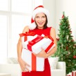 Smiling woman in red dress with gift boxes — Stock Photo #54848581